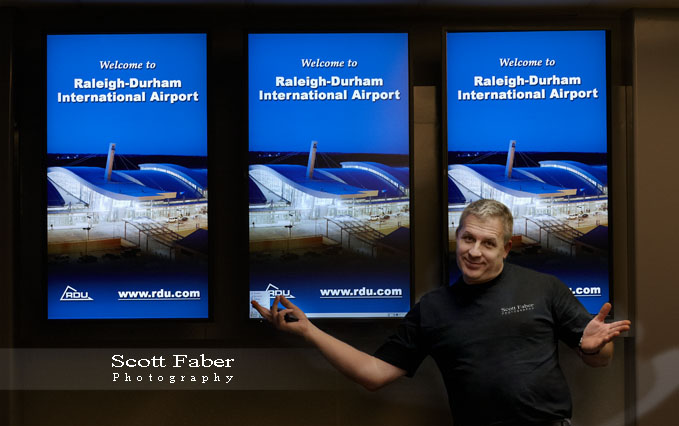 Scott in front of Monitor displaying photo he took of Terminal 2 @ RDU