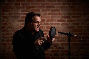 Portfolio headshot of voice actor with microphone in studio