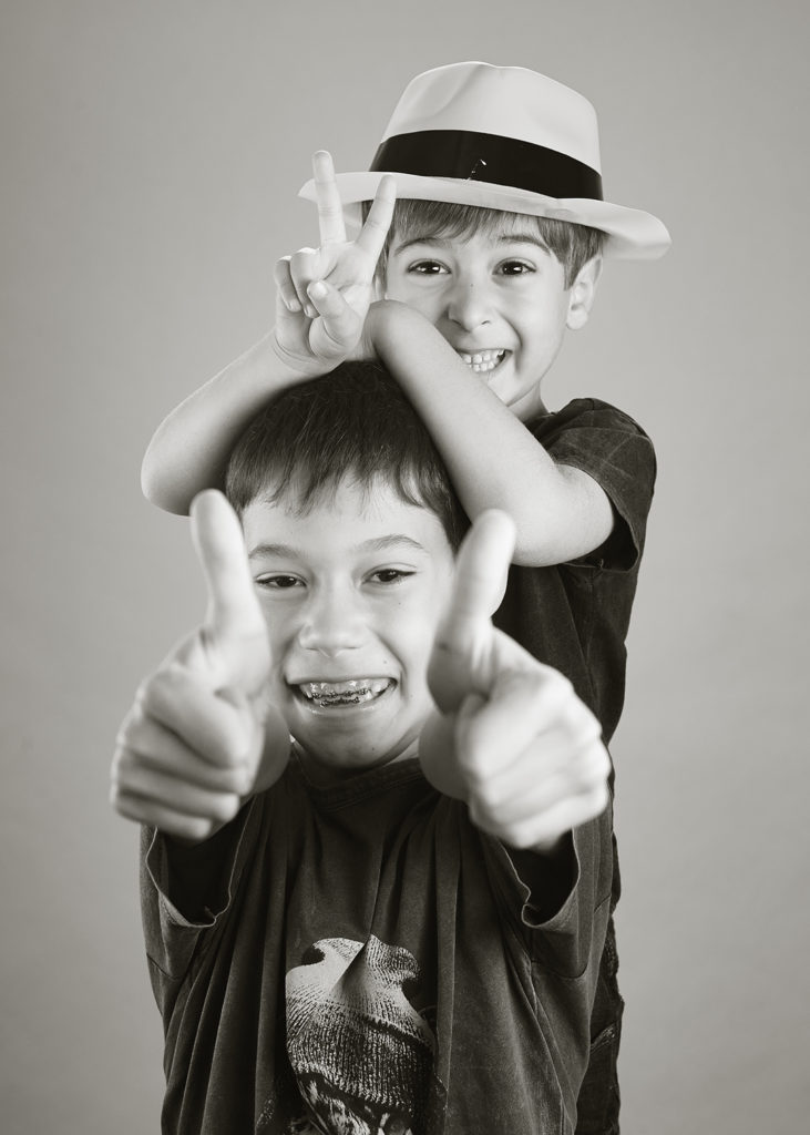 Black and white photo of brothers giving thumbs up and peace sign