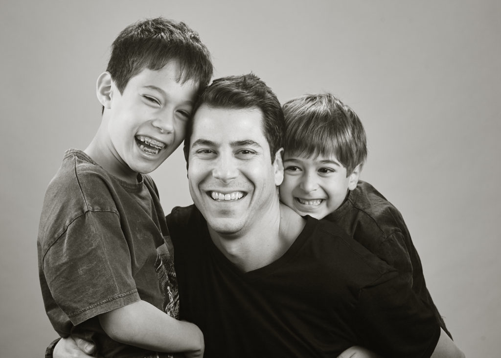 black and white family photo of dad and boys
