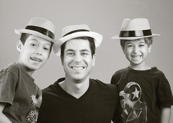 Black and white family photo of dad and boys in hatsin