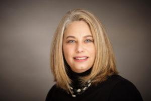 Professional headshot of woman on grey background
