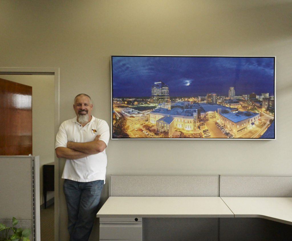 Scott with newly hung framed canvas of Blue Hour From South Bank, chosen by bdb interior design
