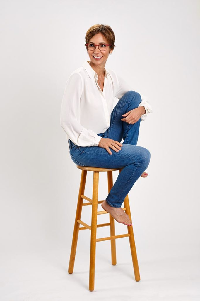 High key portrait of woman on stool